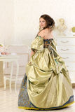Woman in luxury vintage dress standing in bright room Royalty Free Stock Photo