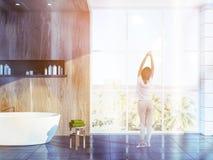 Woman in luxury wooden loft bathroom, morning Stock Photo