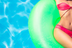 Woman lying on air mattress in swimming pool Stock Photo