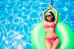 Woman lying on air mattress in swimming pool Royalty Free Stock Images