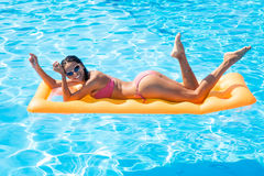 Woman lying on air mattress in the swimming pool Royalty Free Stock Photos