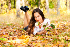 Woman lying on the autumn leaves Stock Image