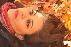 Woman lying on autumn leaves. Beautiful young woman lying on fallen maple leaves in autumn Stock Image