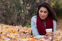Woman lying on autumn leaves with coffee looking away Stock Images