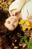 Woman lying on autumn leaves, outdoor portrait Royalty Free Stock Photos