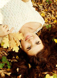 Woman lying on autumn leaves, outdoor portrait Stock Image
