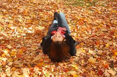 Woman lying on Autumn leaves. Woman with red hair lying supine, eyes closed, on a bed of Autumn leaves in Toronto High Park royalty free stock image