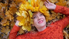 Woman lying on the autumn leaves. Smiling happy woman portrait with wreath, lying in autumn leaves stock video footage