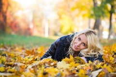 Woman lying in the autumn park Royalty Free Stock Images