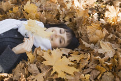 Woman Lying On Autumnal Leaves Royalty Free Stock Image
