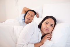 Woman lying awake next to her sleeping boyfriend Stock Photography