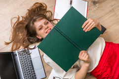 Woman lying on back and covering her face with book Royalty Free Stock Images