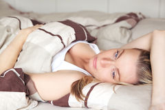 Woman lying back on her bed daydreaming Royalty Free Stock Photography