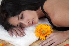 Woman lying on bamboo mat at spa. Surrounded by flower petals stock image