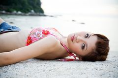 Woman lying on the beach stock images