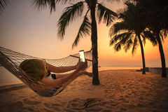 Woman lying in beach cradle and taking a photograph by smart pho Royalty Free Stock Photos