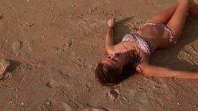 Woman lying on the beach stock video