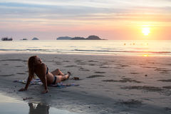 Woman lying on the beach under the rays of the setting sun. Stock Photography