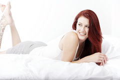 Woman lying on bed Stock Images