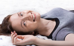 Woman lying on the bed. Beautiful woman in cloth lying on the bed close up Stock Photo