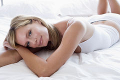 Woman lying in bed royalty free stock photos