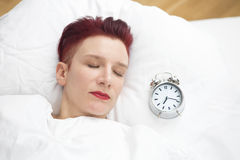 Woman lying in bed with alarm clock on pillow Stock Image