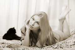 Woman lying at the bed with balck cat. Royalty Free Stock Images