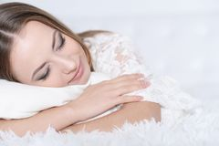 Woman lying on bed. Beautiful young woman lying on soft  bed Stock Image