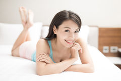 Woman lying on bed Stock Image