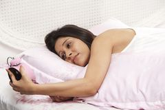 Woman lying on the bed and checking the time Royalty Free Stock Image