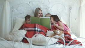 Mother and children reading book stock video footage