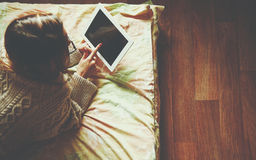 Woman lying in bed with digital tablet Stock Images