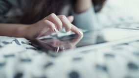 Woman lying in bed with digital tablet touching with finger. View from above stock footage