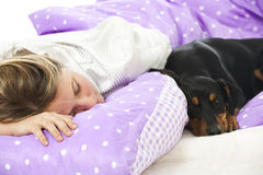 Woman lying in bed with dog Stock Photography