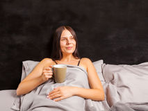 Woman lying in bed and drinking morning coffee. Stock Photos