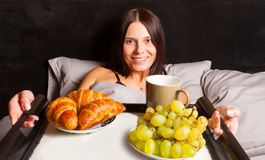 Woman lying in bed and drinking morning coffee. Royalty Free Stock Photos
