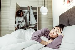 Woman lying in bed feeling tired of her annoying roommate. Annoying roommate. Dark-eyed women lying in bed feeling tired of her annoying roommate stock photo
