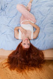 Woman Lying on Bed with Hair Hanging Over the Edge Royalty Free Stock Photography