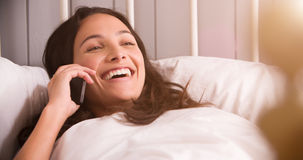 Woman Lying In Bed Having Conversation On Mobile Phone Royalty Free Stock Image