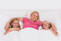 Woman lying in bed with her children Royalty Free Stock Photo
