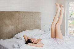 Woman lying on bed with her feet up Stock Image