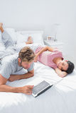 Woman lying on bed while her husband is using a laptop Royalty Free Stock Photos