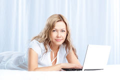 Woman lying on bed with laptop Stock Images