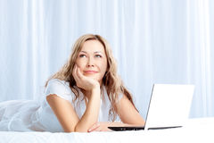 Woman lying on bed with laptop Royalty Free Stock Photo