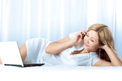 Woman lying on bed with laptop Royalty Free Stock Photos