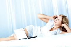 Woman lying on bed with laptop Stock Photos