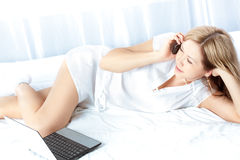 Woman lying on bed with laptop Stock Photo