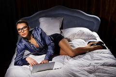 Woman lying on bed with a laptop Royalty Free Stock Photography