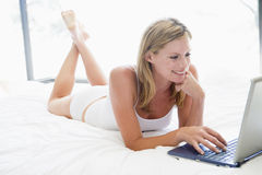 Woman lying in bed with laptop Stock Images