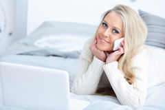 Woman lying on the bed with laptop and phone Stock Photo